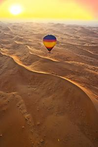 Aerial view of the sand dunes of the Arabian Desert next to Dubai at sunset, United Arab Emirates by Miva Stock
