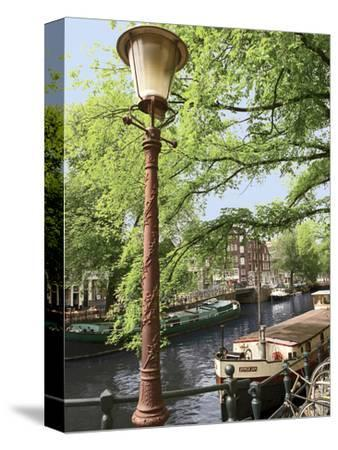 Old Gas Lamp Post and Bicycles on a Bridge over a Canal in Amsterdam, the Netherlands