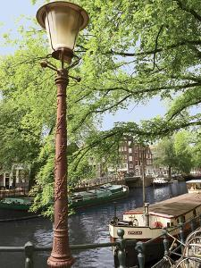 Old Gas Lamp Post and Bicycles on a Bridge over a Canal in Amsterdam, the Netherlands by Miva Stock