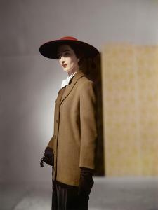 Model Dovima Wearing a Long Straight Jacket, Pen-Stroke Skirt and a Cartwheel Hat