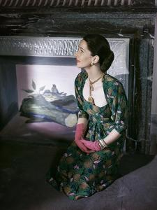 Model Kneeling in Front of Vertes Mural in Fireplace Wearing Green and Pink Print Dress