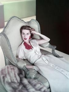 Model Reclining in a Chair Wearing Beige Dress of Slubbed Italian Silk with a Satin Closing