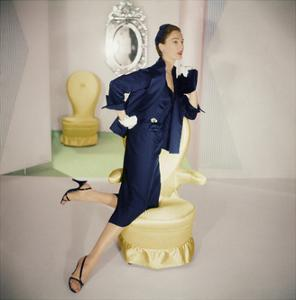 Model Resting Knee on Yellow Armchair Wearing Navy Blue Silk Satin Jacket with Wide Lapel