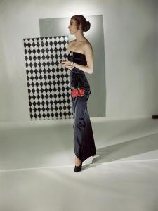 Model Wearing Black Satin Strapless Gown with Rose Motif at the Hip by Adele Simpson