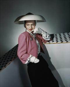 Model Wearing White Hat by Arnold Constable and Pink and Black Skirt Suit by Carolyn Modes