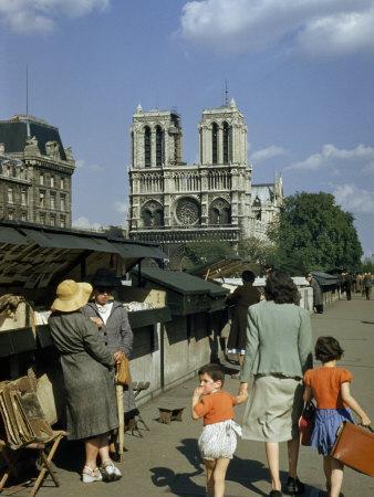 https://imgc.artprintimages.com/img/print/mother-hurries-children-past-book-stalls-near-notre-dame-de-paris_u-l-p8i69o0.jpg?p=0
