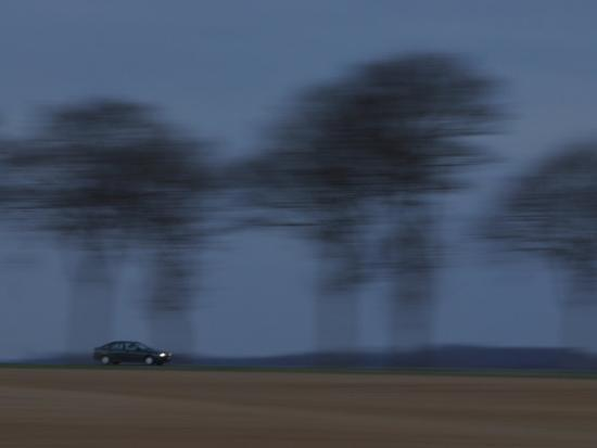 Motion Blur of Speeding Car on Tree-Lined Road in France--Photographic Print