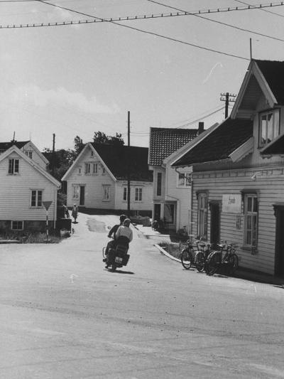 Motorcycle Going Down Street in Small Town--Photographic Print