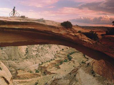 Mountain-Biking over a Natural Arch-Kate Thompson-Photographic Print