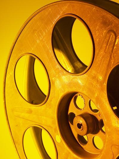 Movie Film and Reels in Yellow Light--Photographic Print