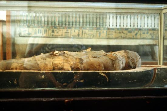 Mummy wrapped in bandages and lying on the base of a coffin, Ancient Egyptian. Artist: Unknown-Unknown-Giclee Print