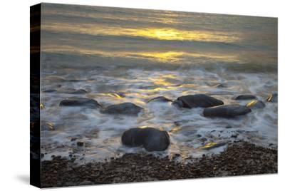 Sun Reflecting on Sea Surface with Rocks on Beach, Scotland, UK, June 2009