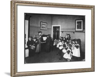 Music Lesson at a German School. One Teacher Plays the Piano--Framed Giclee Print