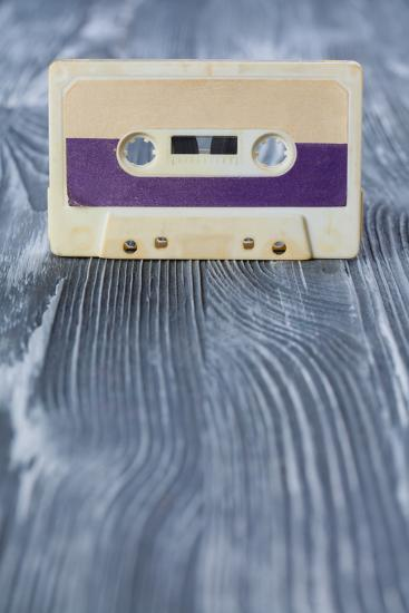 Music Template Postcard. Violet Audio Cassette on the Gray Wooden Background. Vintage, Retro Style.-Besjunior-Photographic Print