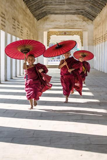 Myanmar, Mandalay Division, Bagan. Three Novice Monks Running with Red Umbrellas in a Walkway (Mr)-Matteo Colombo-Photographic Print