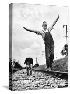Larry Jim Holm with Dunk, His Spaniel Collie Mix, Walking Rail of Railroad Tracks in Rural Area by Myron Davis