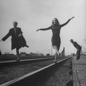Two Young Ballet Russe Dancers Balancing on the Railroad Tracks in the Station While on Tour by Myron Davis