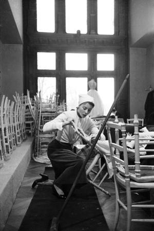 Bettina Graziani Setting Up Seats for Givenchy Runway Show (Will Model In), Paris, France, 1952