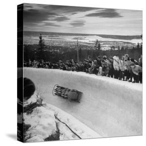 Bobsled Racing by on a Big Vendleboe Curve During the Winter Olympics by Nat Farbman