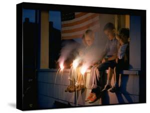 Boys Sitting on Porch Holding Sparklers, with US Flag in Back, During Independence Day Celebration by Nat Farbman