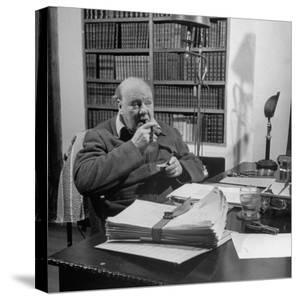 British Leader Winston Churchill Smoking a Cigar at His Desk by Nat Farbman