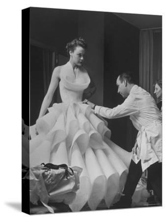Buyer Sampling an Evening Dress on a Model to Check Its Quality