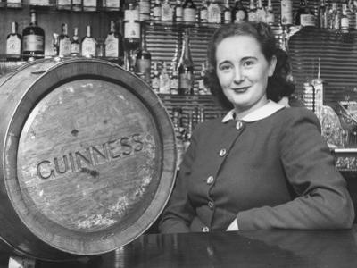 Irish Barmaid at Airport Bar with Keg of Guinness Beer