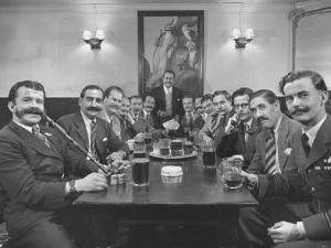Members of Handlebar Club Sitting at Table and Having Formal Beer Session by Nat Farbman