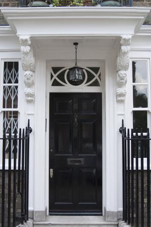 An Old Fashion Black Panel Front Door of a Residential House