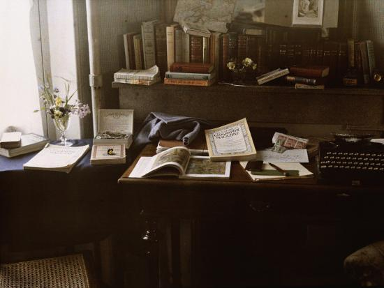 National Geographics Rest on a Desk Near a Typewriter-Maynard Owen Williams-Photographic Print