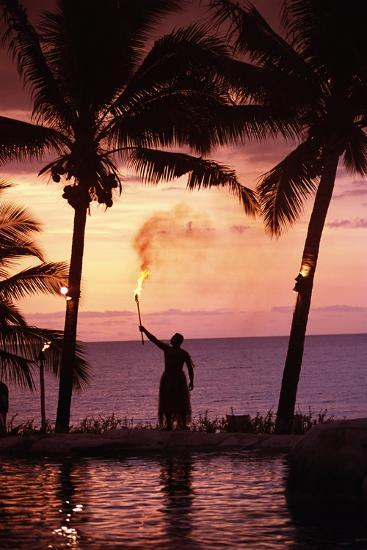 Native in a Grass Skirt Holding a Flaming Torch by Coast at Sunset-Design Pics Inc-Photographic Print