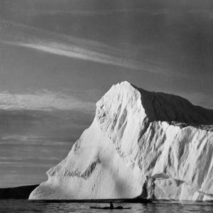 Native Man in Kayak Sitting in Water Next to Iceberg