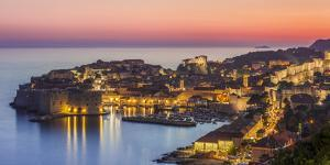 Aerial panorama of Dubrovnik Old Town at night with orange sunset sky, UNESCO World Heritage Site,  by Neale Clark