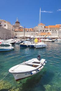 Fishing boat and clear water in the Old Port, Dubrovnik Old Town, Dubrovnik, Dalmatian Coast, Croat by Neale Clark