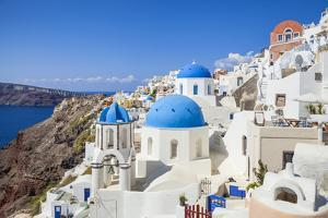 Greek Church with Three Blue Domes in the Village of Oia by Neale Clark
