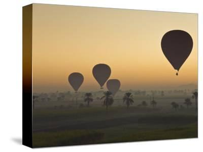 Lots of Hot Air Balloons Flying over the Desert at Sunrise West of the River Nile Near Luxor, Egypt