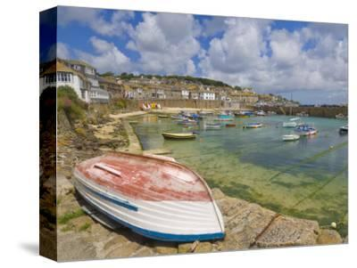 Small Unturned Boat on Quay and Small Boats in Enclosed Harbour at Mousehole, Cornwall, England