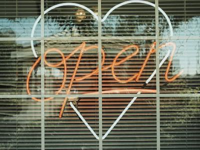 Neon 'Open' sign framed in a heart-shape in a window--Photographic Print