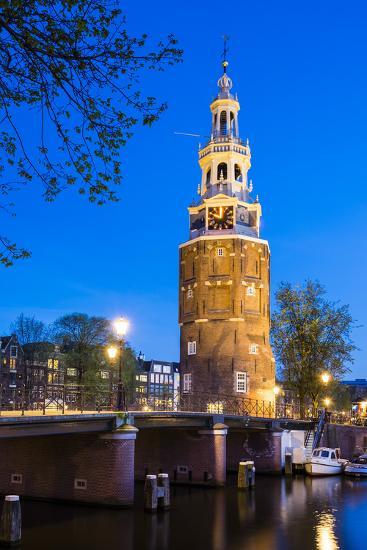 Netherlands, North Holland, Amsterdam. 16th century Montelbaanstoren tower on Oudeschans canal.-Jason Langley-Photographic Print