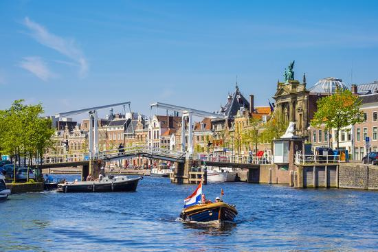 Netherlands, North Holland, Haarlem. A boat in front of the Gravestenenbrug drawbridge on the Spaar-Jason Langley-Photographic Print
