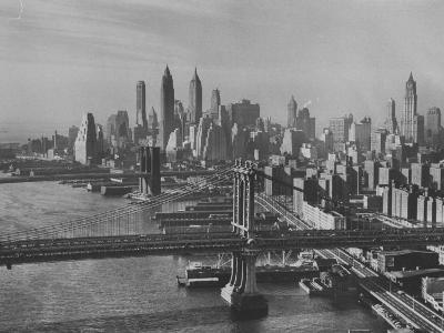 New York City Behind the Brooklyn and Manhattan Bridges That are Hovering over the East River-Dmitri Kessel-Photographic Print