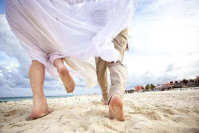 Newlyweds Run Down the Beach on the Riviera Maya in Mexico-Michael Lewis-Photographic Print