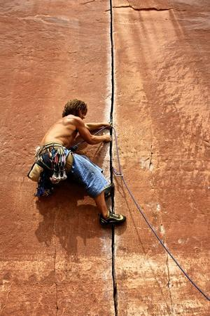 A Climber Expertly Navigating The Thin Finger Crack Running Up The Wall
