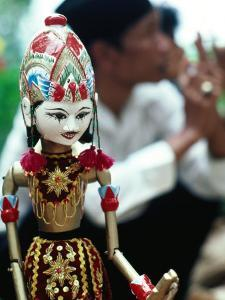 Traditional Puppet with Vendor in Background, Jakarta, Indonesia by Nicholas Pavloff
