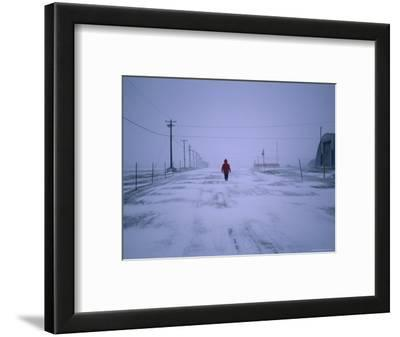Lone Resident Walking on Deserted Street During a Blizzard in Winter, Resolute, Canada