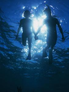 A Couple Swimming Hand-N-Hand, Silhouetted by Sunlight Above by Nick Caloyianis