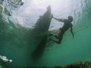 Underwater View of Moken Tribesmen Swimming as He Holds onto a Boat by Nicolas Reynard