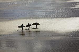 Surfers in Silhouette, Heading Towards the Surf by Nigel Hicks