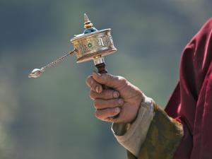 A Buddhist Spins His Hand-Held Prayer Wheel in a Clockwise Direction with the Help of a Weighted Ch by Nigel Pavitt