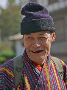 An Old Man at Trashigang Wearing the Traditional Gho Robe of All Bhutanese Men by Nigel Pavitt